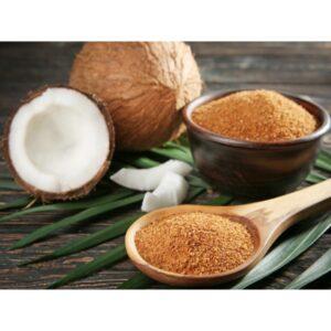 Ζάχαρη καρύδας σε καστανούς κόκκους σε ξύλινη κουτάλα με φόντο καρύδες