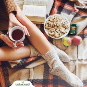 Στην εικόνα φαίνεται το μπουκαλάκι δίπλα σε ένα πιάτο με μπισκότα και σε 2 μήλα πάνω στο κρεβάτι που ένα νεαρό κορίτσι απολαμβάνει το πρωινό της