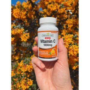 Βιταμίνη C 1000mg low acid Natures Aid 30 δισκία μπροστά από φυτό κυνόροδου